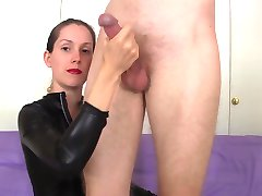 She strokes his cock and balls from behind in her catsuit